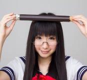 Estudiante asiática en uniforme escolar que estudia con un lápiz de gran tamaño Foto de archivo
