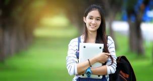 Estudiante asiática hermosa que sostiene los libros y que sonríe en la cámara Fotos de archivo