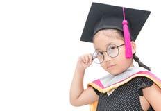 Estudiante asiática linda que piensa en casquillo de la graduación Foto de archivo