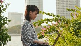 Estudiante asiática vietnamita que usa el ordenador portátil en centro de ciudad metrajes