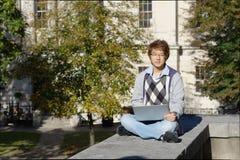 Estudiante asiático al aire libre con el ordenador portátil Foto de archivo