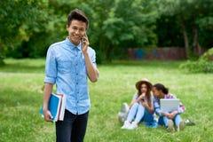 Estudiante asiático alegre en césped del campus Fotos de archivo libres de regalías