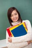 Estudiante asiático bastante joven que abrocha ficheros Imagen de archivo libre de regalías