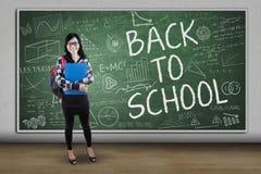 Estudiante asiático con el texto de nuevo a la escuela Fotografía de archivo