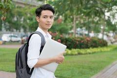 Estudiante asiático con la computadora portátil Fotos de archivo