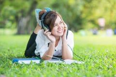 Estudiante asiático con los auriculares al aire libre Disfrutar de música Foto de archivo libre de regalías