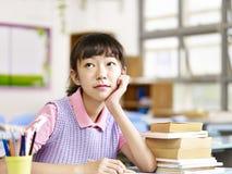 Estudiante asiático de la escuela primaria que piensa en sala de clase Imagen de archivo libre de regalías