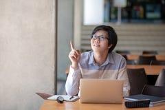 Estudiante asiático del hombre que señala el finger en biblioteca de universidad fotografía de archivo libre de regalías