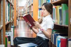 Estudiante asiático en la lectura uniforme en la biblioteca en la universidad Fotos de archivo