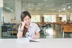 Estudiante asiático en libro de lectura uniforme en la sala de clase Fotos de archivo libres de regalías