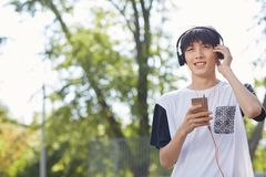 Estudiante asiático feliz en auriculares en un fondo de la calle Concepto adolescente del estilo Copie el espacio Fotos de archivo
