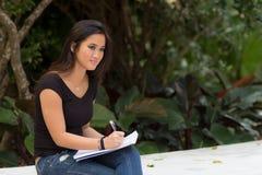 Estudiante asiático femenino que se sienta fuera de la escritura en diario del cuaderno Imagen de archivo libre de regalías