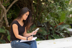 Estudiante asiático femenino que se sienta fuera de la escritura en diario del cuaderno Fotografía de archivo libre de regalías
