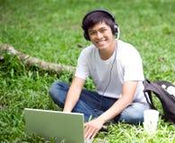 Estudiante asiático hermoso joven con el ordenador portátil y la sonrisa en al aire libre Fotografía de archivo libre de regalías