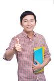 Estudiante asiático joven con el libro que muestra el pulgar para arriba Imágenes de archivo libres de regalías