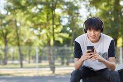Estudiante asiático joven con un nuevo smartphone y auriculares en un fondo de la calle Concepto de la tecnología Copie el espaci Imágenes de archivo libres de regalías