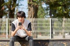Estudiante asiático joven con un nuevo smartphone y auriculares en un fondo de la calle Concepto de la tecnología Copie el espaci Foto de archivo