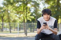 Estudiante asiático joven con un nuevo smartphone y auriculares en un fondo de la calle Concepto de la tecnología Copie el espaci Fotos de archivo libres de regalías