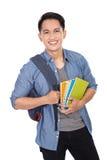 Estudiante asiático joven con una mochila encendido y sosteniendo los libros Foto de archivo libre de regalías