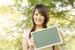 Estudiante asiático joven de la estudiante universitaria con la pizarra en blanco Imagen de archivo