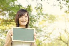 Estudiante asiático joven de la estudiante universitaria que sostiene la pizarra en blanco Fotografía de archivo