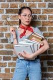Estudiante asiático pensativo que sostiene los libros y el lápiz Fotografía de archivo libre de regalías