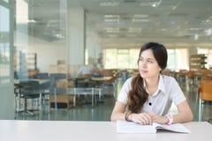 Estudiante asiático que se pregunta o que piensa en algo Imagen de archivo