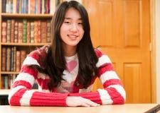 Estudiante asiático que se sienta en el escritorio en sala de clase Imágenes de archivo libres de regalías