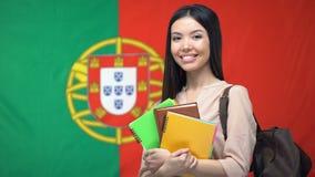 Estudiante asiático que sostiene cuadernos contra fondo portugués de la bandera almacen de video