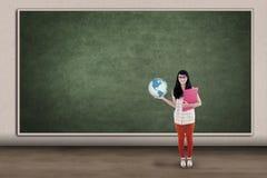 Estudiante asiático que sostiene el globo en clase Imagenes de archivo