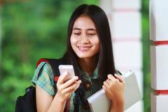 Estudiante asiático sonriente que celebra el libro y la lectura del mensaje de texto Fotografía de archivo