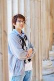 Estudiante asiático sonriente que sostiene los libros al aire libre Imagen de archivo