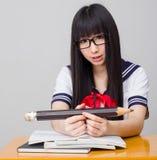 Estudiante asiática en uniforme escolar que estudia con un lápiz de gran tamaño Imagenes de archivo