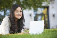 Estudiante asiático que estudia en el ordenador portátil Fotos de archivo libres de regalías