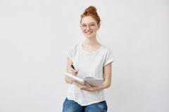 Estudiante astuto hermoso que sonríe sosteniendo el cuaderno Imagen de archivo