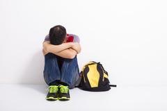 Estudiante aterrorizado que se sienta en el piso Fotografía de archivo libre de regalías