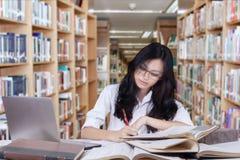 Estudiante atractivo con el pelo largo que estudia en biblioteca Foto de archivo libre de regalías