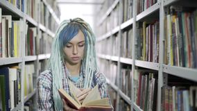 Estudiante atractivo del inconformista que hojea a trav?s del libro mientras que estudia en biblioteca con el fondo del estante almacen de video
