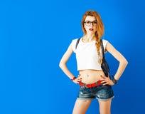 Estudiante atractivo Hipster Girl en fondo azul foto de archivo
