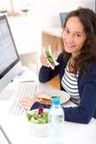 Estudiante atractivo joven que come el bocadillo mientras que trabaja Imágenes de archivo libres de regalías