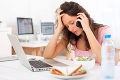 Estudiante atractivo joven que come la ensalada mientras que llama por teléfono Fotografía de archivo