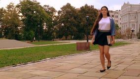 Estudiante atractivo que camina en la calle almacen de metraje de vídeo