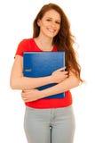 Estudiante atractivo que sostiene carpetas aisladas sobre el backgroun blanco Foto de archivo