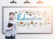 Estudiante barbudo sonriente y un bosquejo de la educación Imágenes de archivo libres de regalías