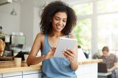 Estudiante bastante africano que descansa en el café que sonríe mirando la pantalla de la tableta Fotos de archivo libres de regalías