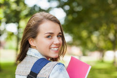 Estudiante bastante alegre que sonríe en el cuaderno que lleva de la cámara Imagen de archivo