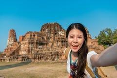 Estudiante bastante feliz que se coloca en Ayutthaya Imagenes de archivo