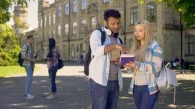 Estudiante biracial elegante que ayuda a su fellowmate rubio con los hometasks de las matemáticas metrajes
