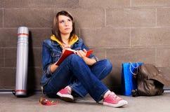 Estudiante bonito cerca de la escritura de la pared en el cuaderno Foto de archivo libre de regalías