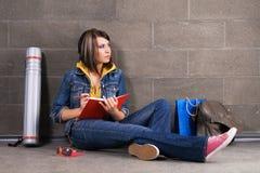 Estudiante bonito cerca de la escritura de la pared en el cuaderno Imagen de archivo